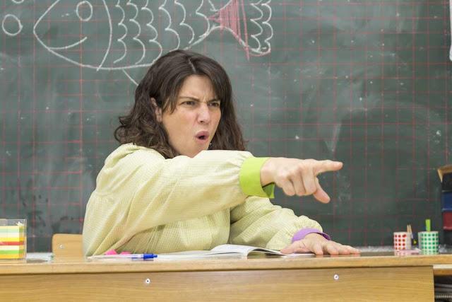 Professora sentada em sala de aula brava repreendendo aluno