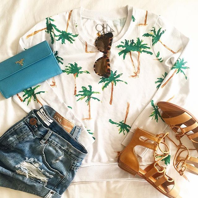 one teaspoon husk bandit shorts, palm tree sweatshirt, BC footwear sandals, karen walker sunglass dupes, blue prada wallet, beach outfit idea with jean shorts, vacation outfit idea
