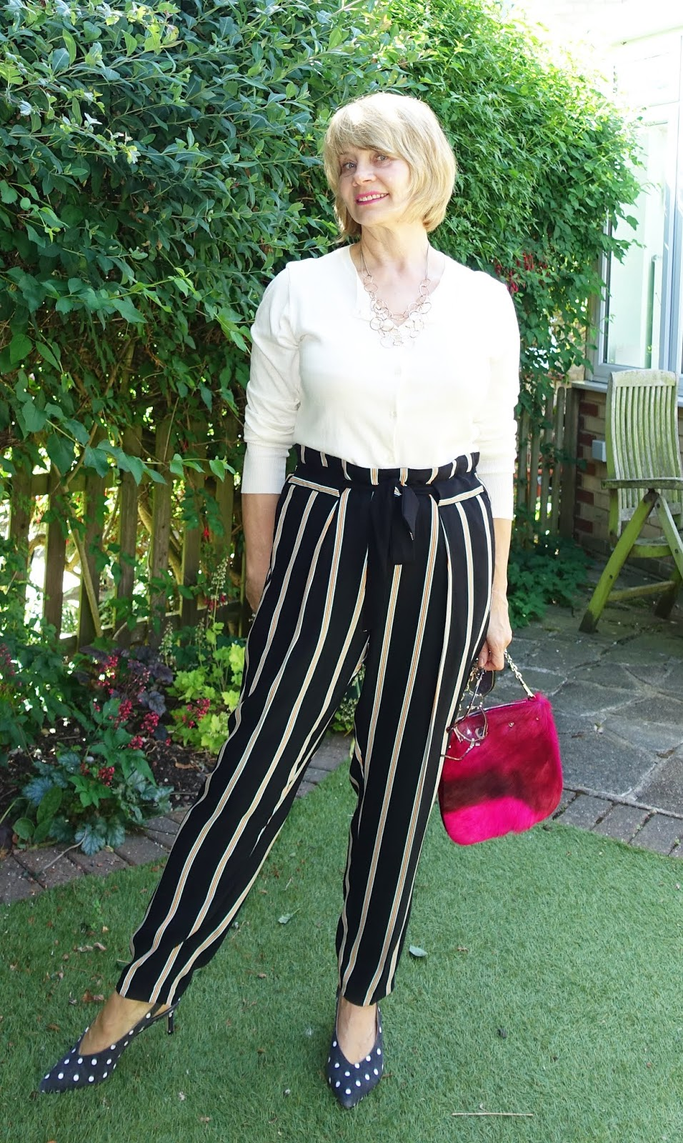 Striped trousers worn with polka doe kitten heels and a white cardigan