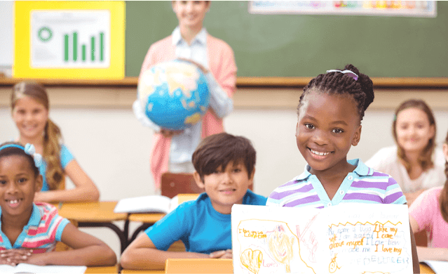 Photo of proud girl holding up her work in the classroom with students and teacher behind her.