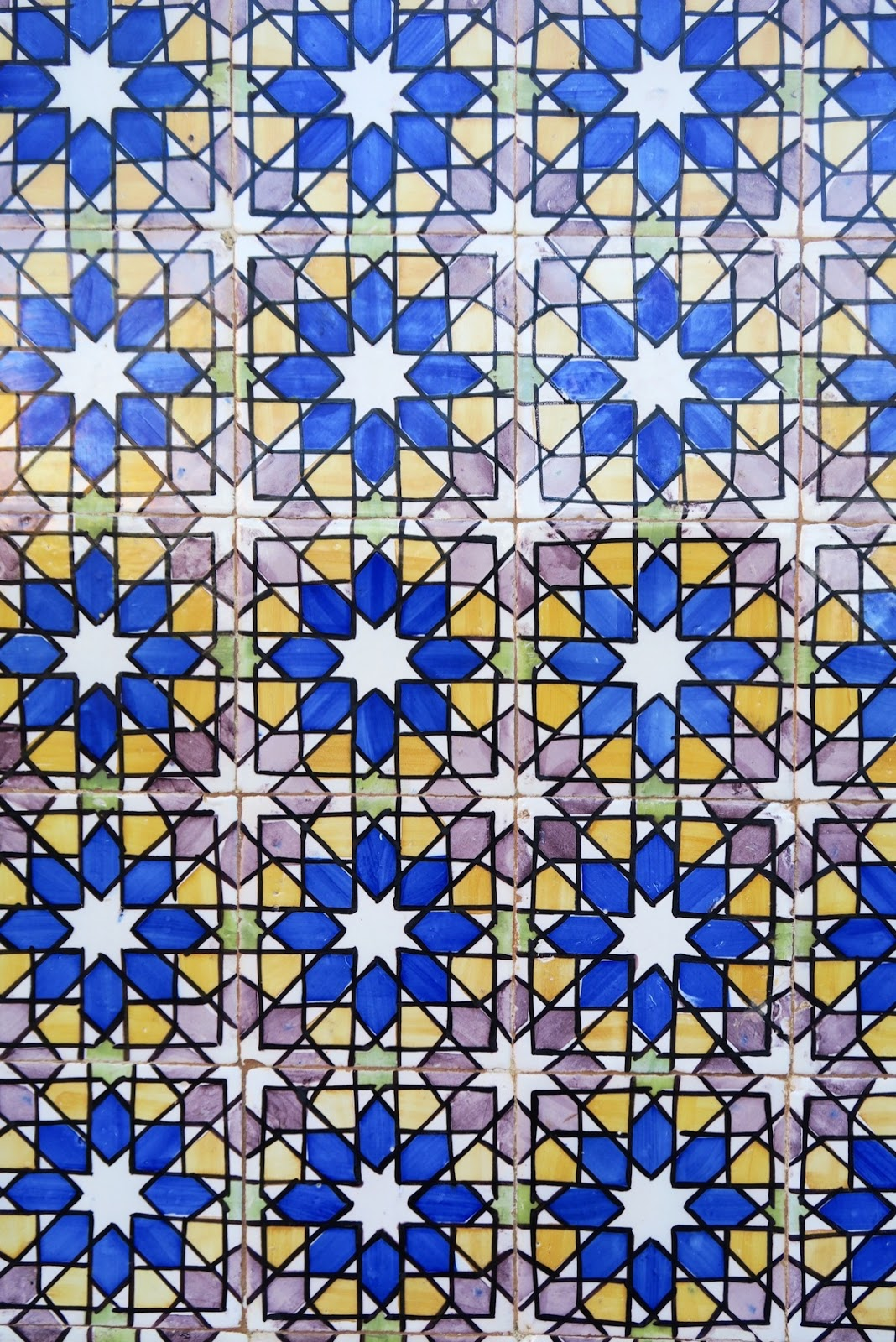 This is a close-up of beautiful tile work at the Pena Palace in Sintra Portugal. This is a beautiful star pattern mixed with blue, yellow, red and even green tiles.