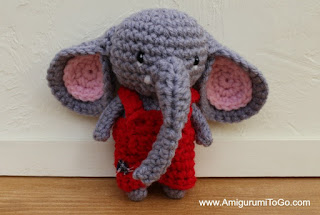 small crochet elephant in red overalls