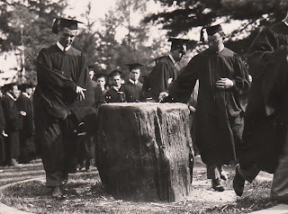 A group of figures in caps and gowns. In the foreground, two men are touching a tree stump.