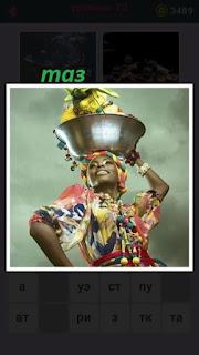 женщина несет таз на своей голове в национальной одежде