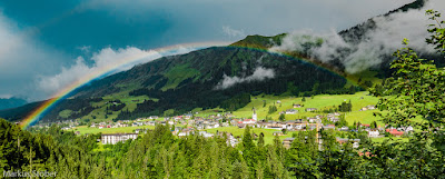 [picture of small town surrounded by grass, with rainbow overhead]