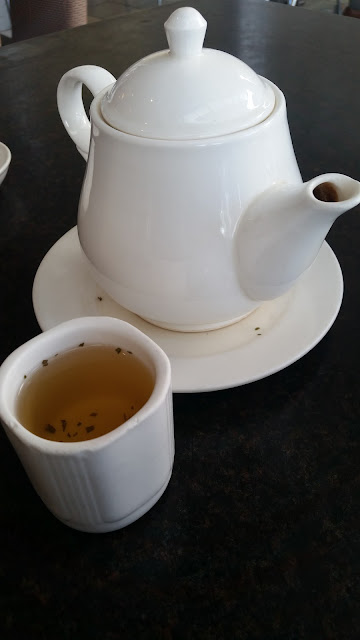 Refreshing hot tea served in a cup with the white tea pot