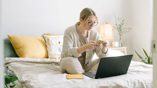 Vrouw op bed thuiswerk