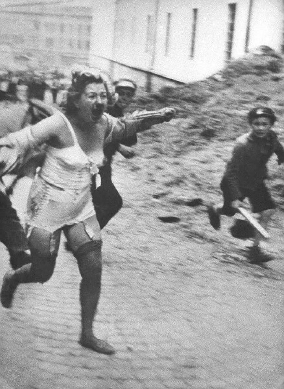Woman chased by men and youth armed with clubs, Medova Street in Lviv, July 1941.