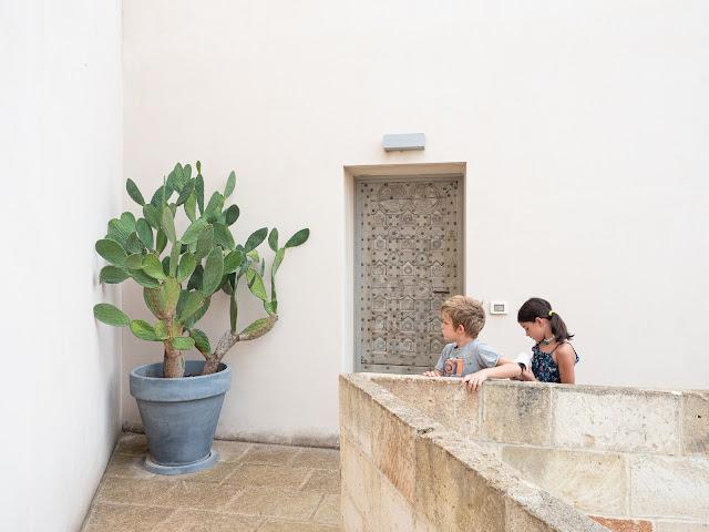Niños frente a la puerta de entrada al apartamento con cactus enorme
