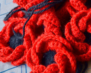 A pile of crocheted poppies in close-up with black centres and red petals with black threads attached on their backs for stitching them onto something later.