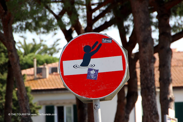 A sticker with one person jumping out of sea put on a regular No entry-street sign.