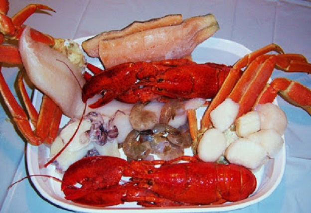 this is a shellfish variety of seafood in a white casserole dish all raw