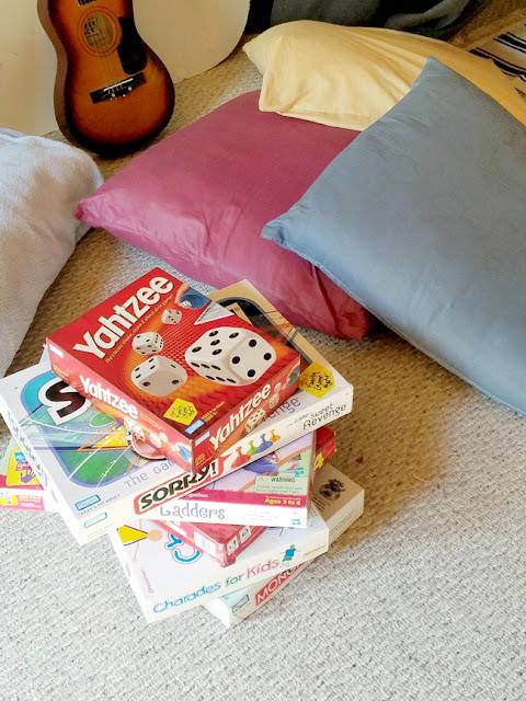 board games, pillows, guitar in basement floor.