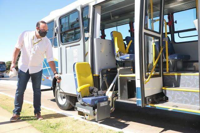 A imagem mostra um homem andante com máscara acionando o elevador da cadeira do ônibus adaptado as pessoas com deficiência
