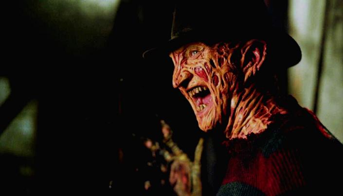 """Imagem: Personagem Freddy Krueger de """"Hora do Pesadelo"""", Homem branco cuja a pele foi queimada e está cheia de cicatriz, ele usa chapéu de caubói e blusão de lã vermelha com verde. Ele sorri diabolicamente enquanto levanta a mão que tem uma luva com garras de ferro."""