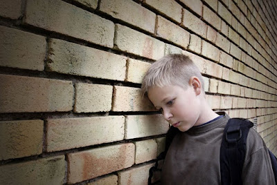 lonely boy leaning against a wall