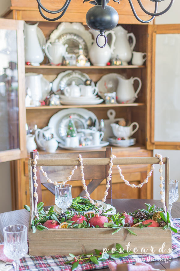 Christmas table with centerpiece of wooden toolbox with greenery and pomegranates