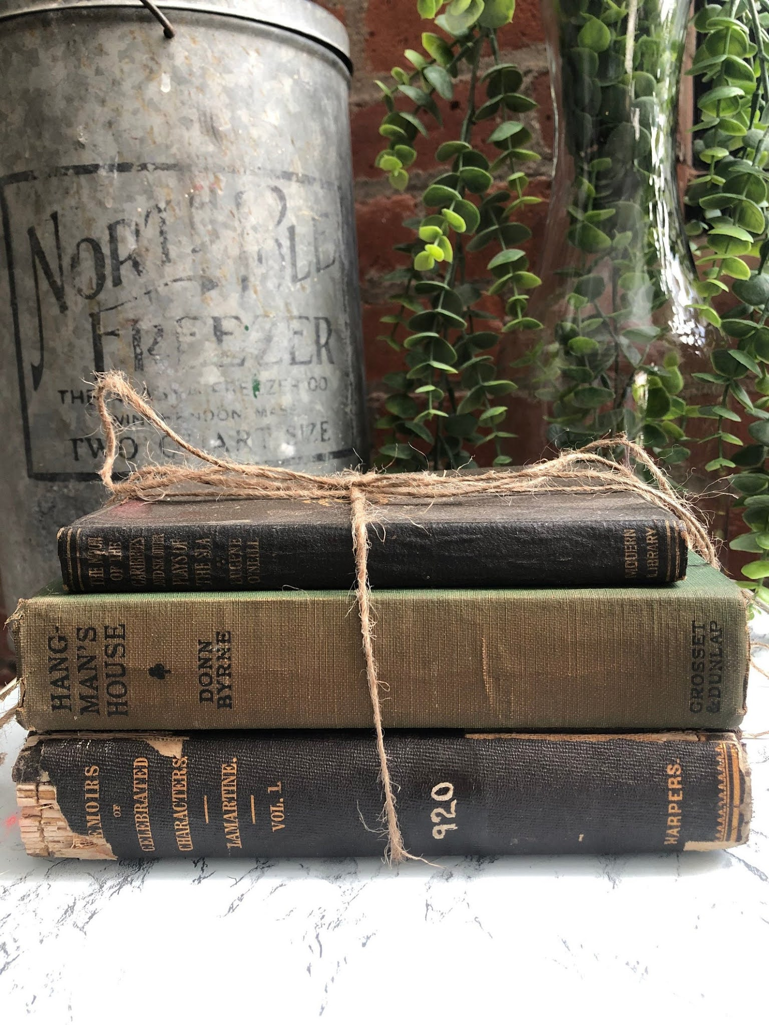 A stack of three antique books tied with string