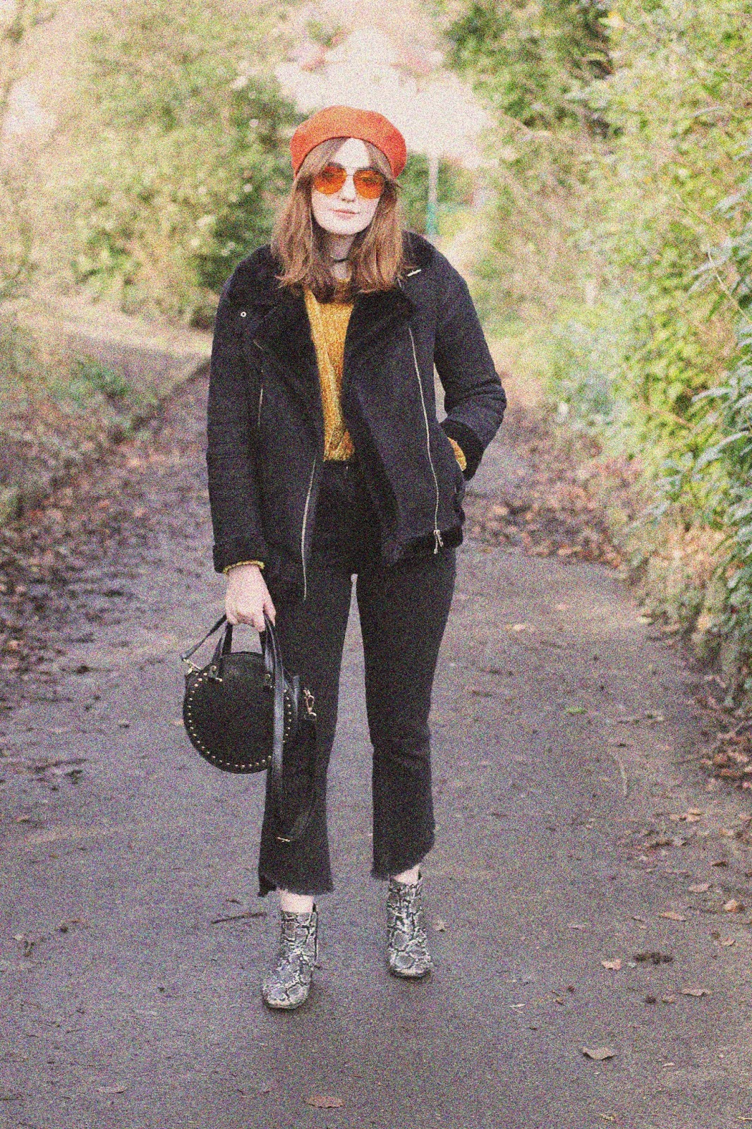 that 70s show inspired outfit featuring orange beret and aviator sunglasses, black faux shearling aviator jacket, mustard chenille jumper, black kick flare raw hem jeans and snake print ankle boots with black studded circle bag with 70s grain effect photo filter