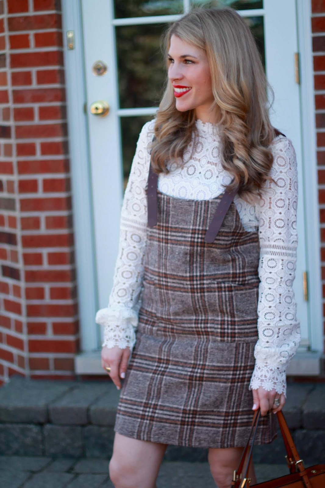 brown plaid jumper, white lace blouse, white pumps, cognac tory burch tote