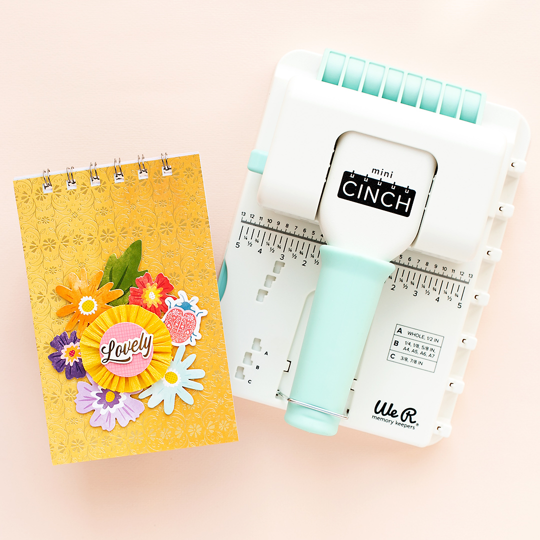 Spiral bound mini album with floral embellishments and the Mini Cinch by We R Memory Keepers