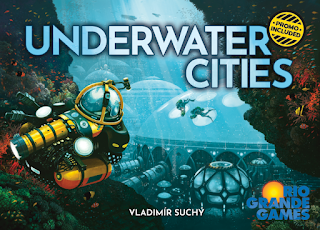 The box cover art: a view of a series of domed underwater habitats, with a couple of people in scuba gear swimming nearby, and a submersible working vehicle in the foreground.
