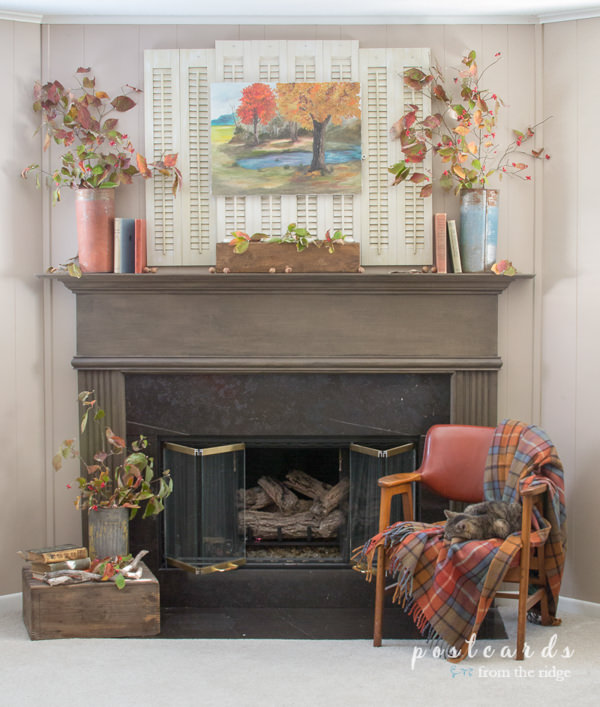 brown fireplace mantel with shutters, old books, leaves, mid century chair with plaid blanket