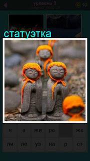 стоит несколько статуэток с платками оранжевого цвета на головах