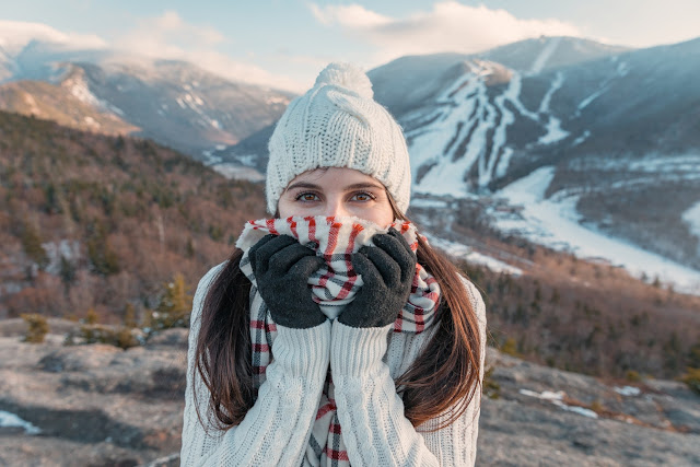 girl wearing sweater, warm hat, scarf and gloves in the mountains