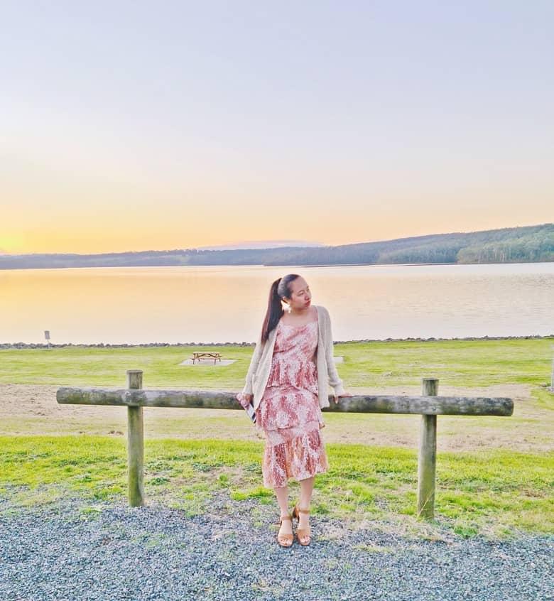 a girl wearing a dress overlooking a lake