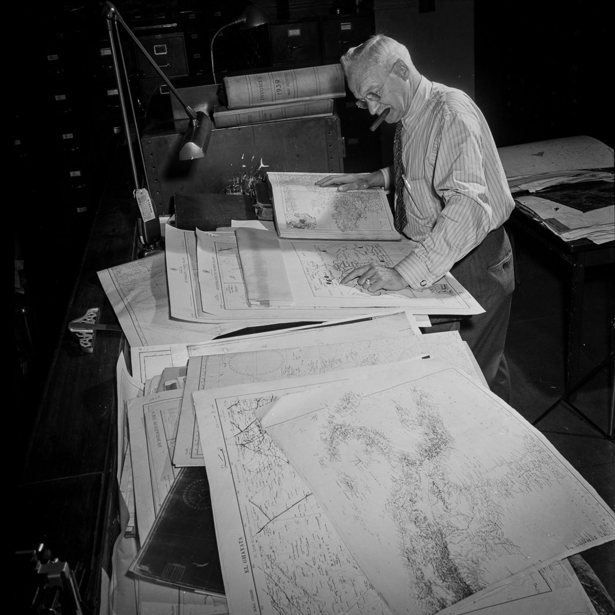 In the art department, the cartographer consults charts to prepare a map of the war in Europe. This employee was also here for the First World War.