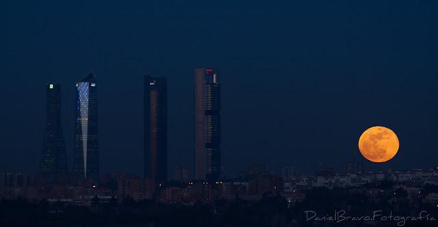 Fotografía de las 4 Torres de Madrid con la Luna llena de color naranja y muy cerca de ellas anocheciendo.