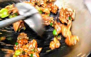 Stir frying chicken manchurian in a wok