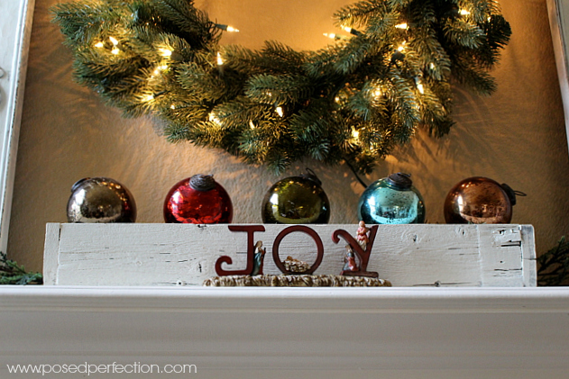 Rustic wooden box filled adorned with shiny colored glass balls and Joy nativity in front.