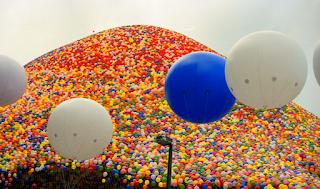 Tausende bunte Luftballons schweben am Himmel.