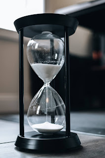 an hourglass with white sand falling
