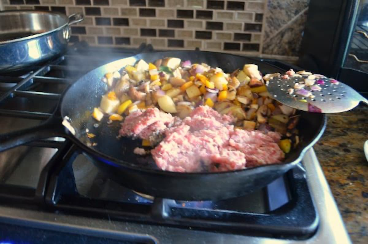 Breakfast Potatoes with sausage to cast iron pan being cooked for Breakfast Burritos recipe.