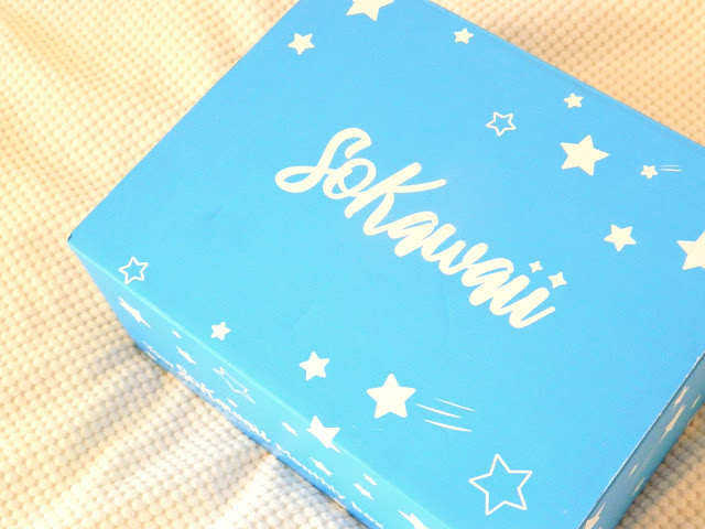 A photo showing a light blue box sitting on a cream blanket, the word 'so kawaii' is printed across the top