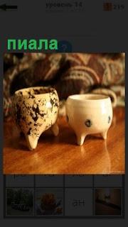На столе стоят две чашки пиала, в деревянном исполнении на ножках
