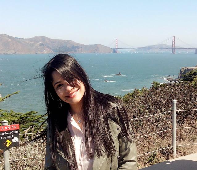 menina do cabelo preto sorrindo em frente ao mar