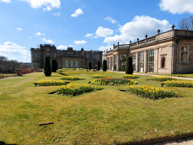 A view of Lyme house across the gardens with the orangery on the right.  There are ornate borders filled with narcissi