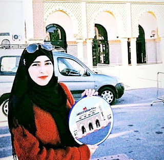 صورة المبدعة حسناء سانمي تحمل إحدى لوحاتها