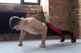 homem fitness fazendo exercício físico em casa sem camisa