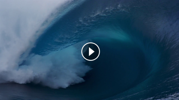 Surfers Paddle Over Enormous Wave in Tahiti