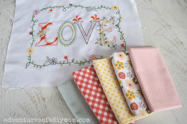 embroidery spelling the word love and several coordinating bundles of fabric
