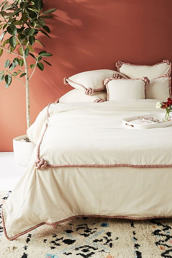 The terracotta wall color makes a lovely backdrop for the plant and bedding- design addict mom