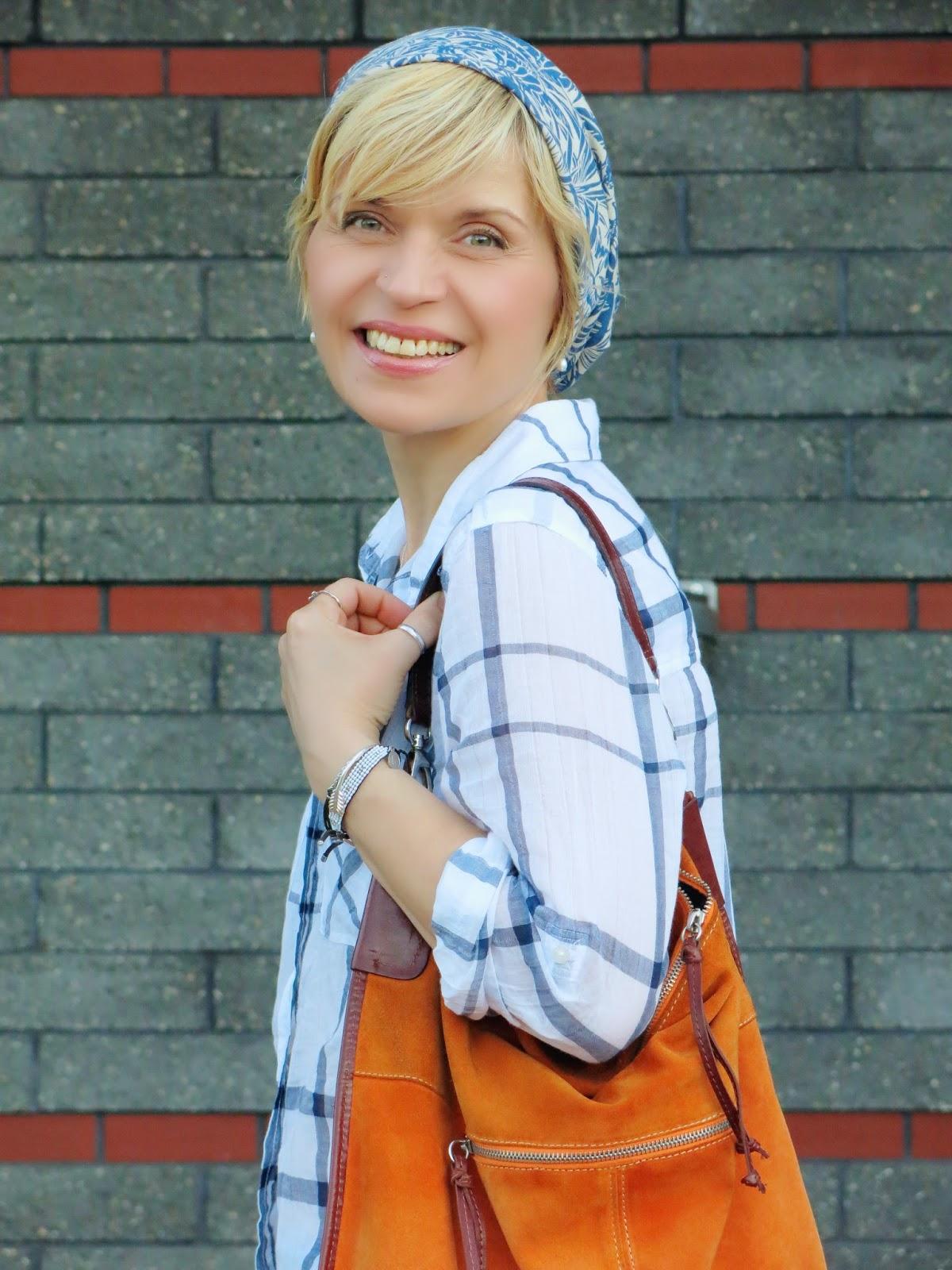 a white plaid shirt, orange suede bag, and summer beanie