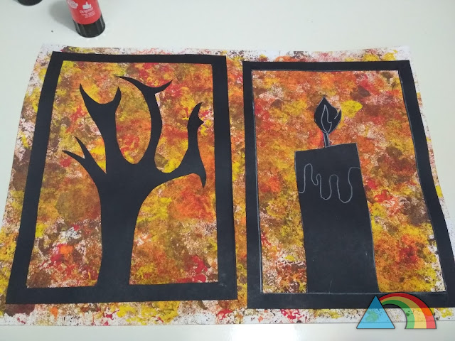 Cartulina pintada con esponja de colores otoñales (rojo, marrón, amarillo y naranja) con silueta de cartulina negra de árbol y vela