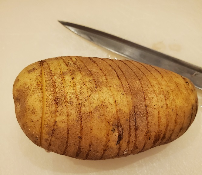 this is a washed and sliced potato called fan potatoes or hasselback on a cutting board