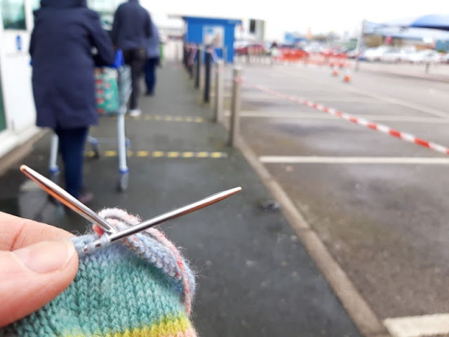 Image shows a close up of knitting on needles.  In the background are supermarket shoppers waiting in a queue